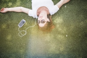 Overhead view of mid adult woman listening to earphones in park